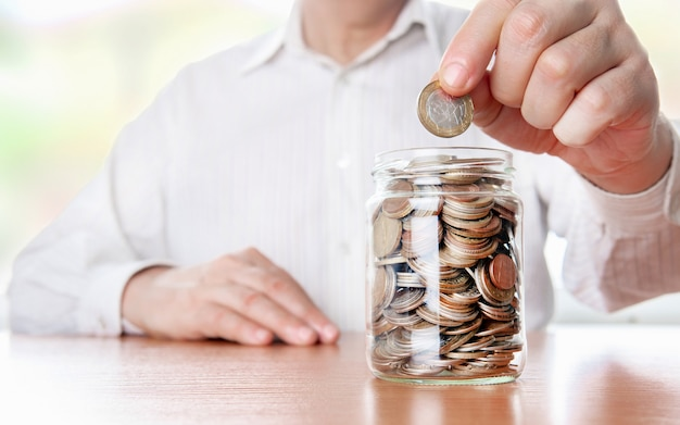 Pieniądze w szklanym słoiku. ręka kładzie monetę na rozwój. koncepcja inwestycji. wzrost gospodarczy. zarządzanie biznesem. akumulacja kapitału.