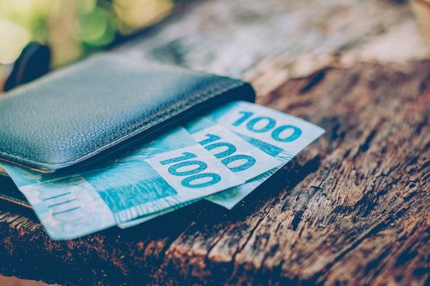 Pieniądze z brazylii. prawdziwe banknoty, brazylijska waluta w czarnym portfelu. pojęcie finansów, gospodarki i bogactwa.
