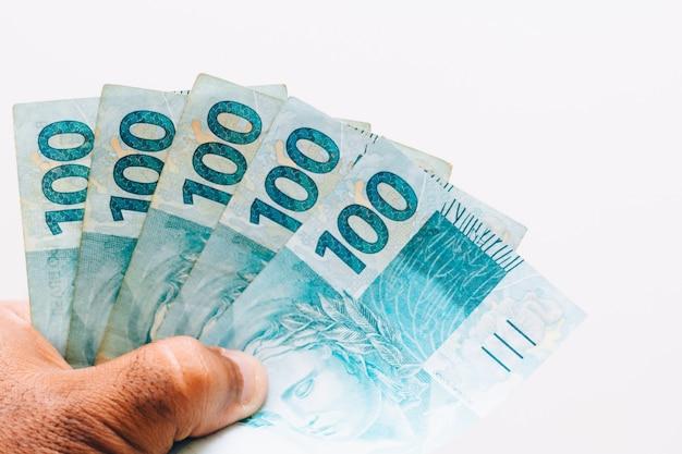Pieniądze z brazylii. prawdziwe banknoty, brazylijskie pieniądze w ręce czarnego mężczyzny. nuty 100 reali. pojęcie inflacji, gospodarki i biznesu. jasne tło