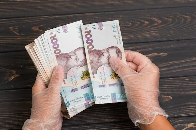 Pieniądze z ukrainy. stos banknotów hrywny ukraińskiej w rękawiczkach na drewnianym stole. hrywna 1000 uah