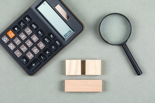 Pieniężna analiza i księgowości pojęcie z magnifier, drewniani bloki, kalkulator na szarego tła odgórnym widoku. obraz poziomy