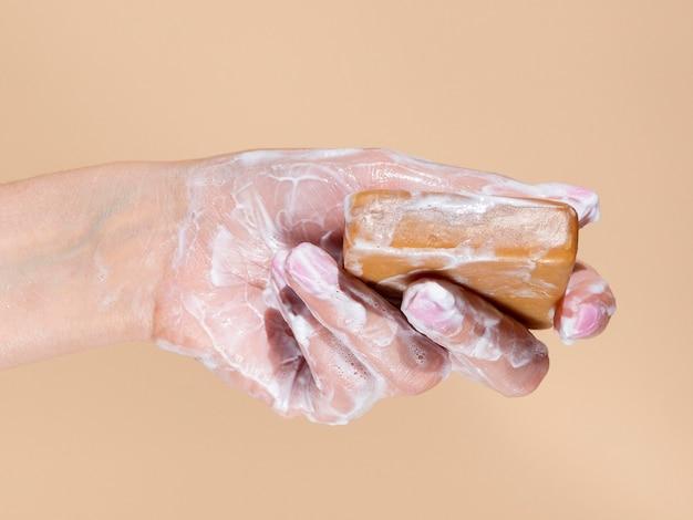 Pienista dłoń trzymająca kostkę mydła