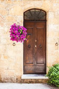 Pienza, region toskanii, włochy. stare drzwi wykonane z drewna z kwiatami