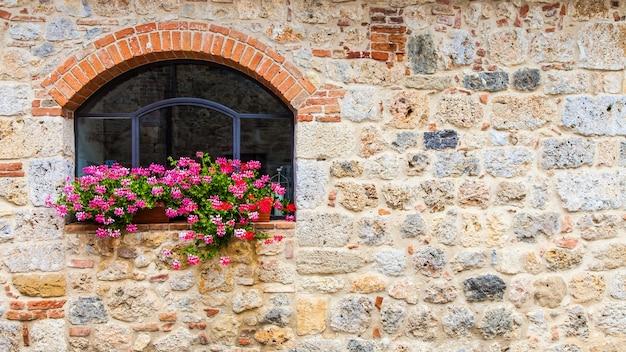 Pienza, region toskanii, włochy. stare okno z kwiatami