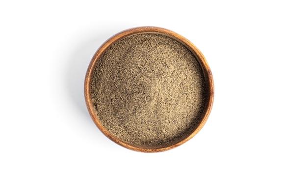 Pieprz czarny mielony w misce drewniane na białym tle na białym tle. wysokiej jakości zdjęcie