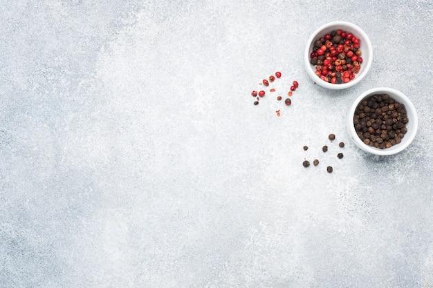 Pieprz groszek czarno-czerwony na talerzach, szary betonowy stół, miejsce na kopię.