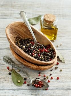 Pieprz wymieszać w misce, liście laurowe i oliwę z oliwek na drewnianym stole