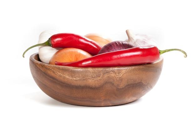 Pieprzowy chili, cebula i czosnek w drewnianym pucharze odizolowywającym na białym tle