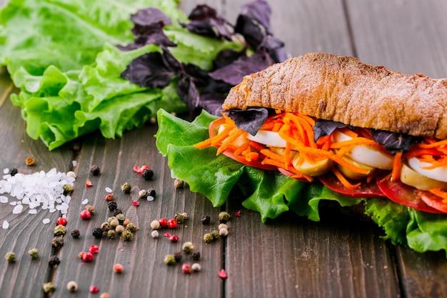 Pieprzu, soli i zieleni leżą przed zdrową kanapką pełnoziarnistą
