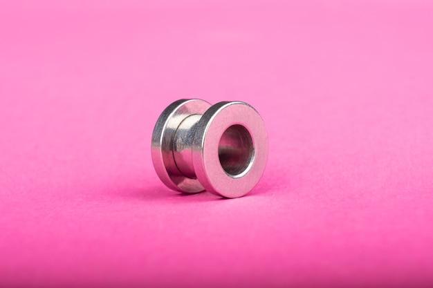 Piercing srebrny tunel do ucha na różowym tle zbliżenia