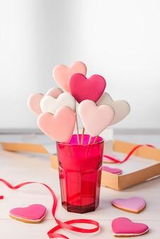 Piernik na patyku w kształcie serc w jasnym różowym szkle na lekkim stole. walentynki.