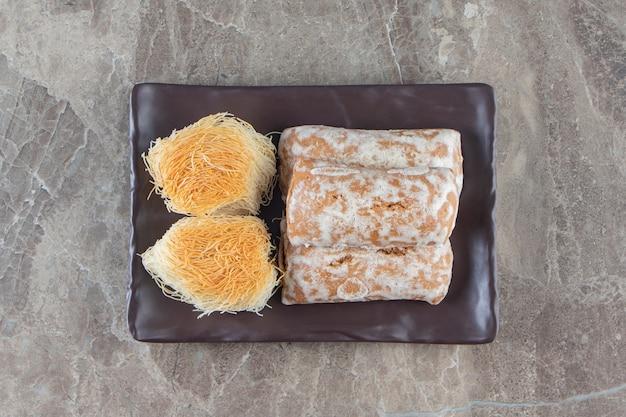 Piernik z konfiturą w cukrowej glazurze i kadayifem na półmisku na marmurze.