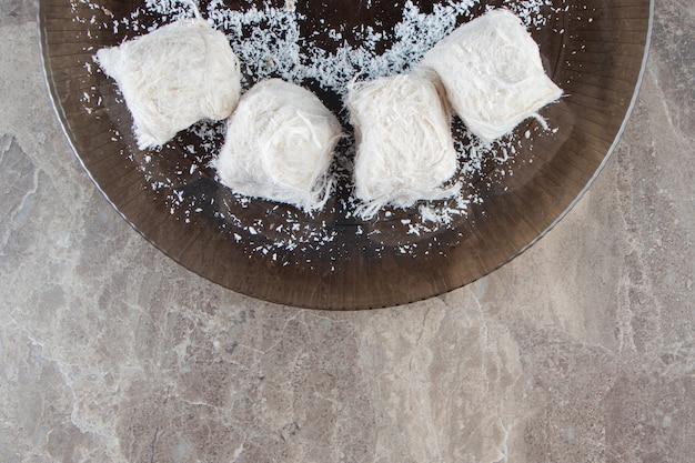Piernik z konfiturą w cukrowej glazurze i watą cukrową na talerzu, na marmurze.