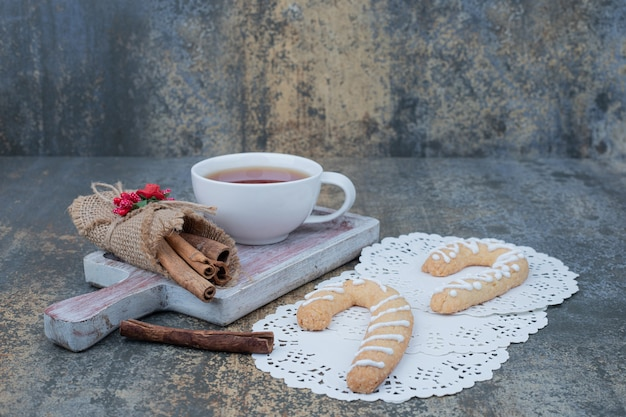 Pierniki, cynamon i filiżanka herbaty na marmurowym stole. wysokiej jakości zdjęcie