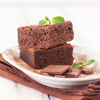 Pierniki czekoladowe kwadratowe kawałki w stos na białym talerzu ozdobione liści mięty