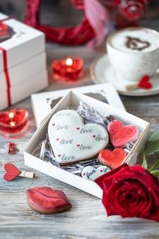 Pierniki, filiżanka kawy, kwiat róży i wieniec w kształcie serca