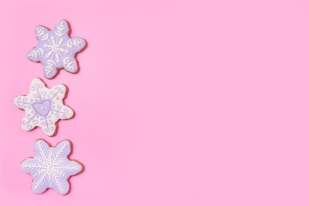 Pierniki gwiazdy płatki śniegu na słodkim różowym tle. widok z góry.
