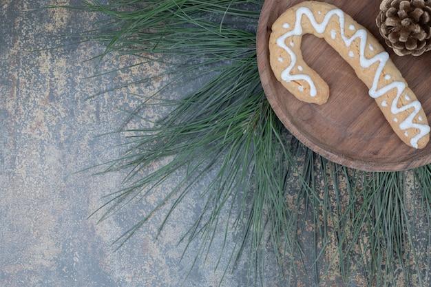 Pierniki i szyszka na drewnianym talerzu. wysokiej jakości zdjęcie