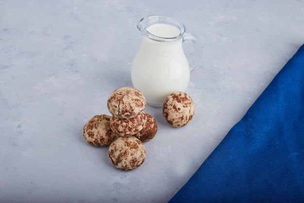 Pierniki kakaowe na białym tle na szarym tle z słoikiem mleka.
