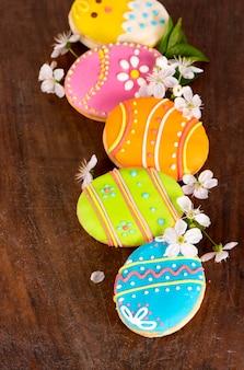 Pierniki w postaci kolorowych jajek na ciemnym tle drewnianych. wesołych świąt wielkanocnych. jasne ciastka. smakołyki dla dzieci. skopiuj miejsce