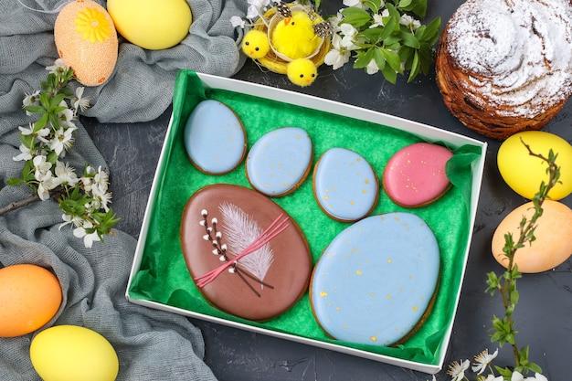 Pierniki wielkanocne w postaci kolorowych jajek w pudełku na ciemnym tle