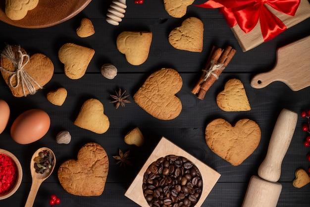 Piernikowe ciasteczka w kształcie serca, przyprawy, ziarna kawy i artykuły do pieczenia.