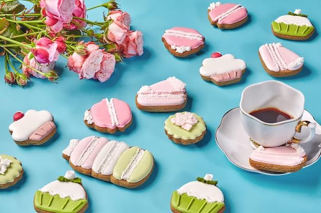 Piernikowe ciasteczka z cukrem pudrem filiżanka kawy i róż
