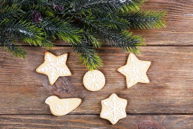 Piernikowe ciasteczka z świąteczną dekoracją na drewnianym stole w tle