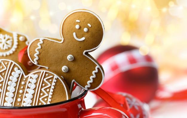 Piernikowe ludziki i świąteczne ciasteczka w czerwonym kubku na świąteczne bombki i światła w tle