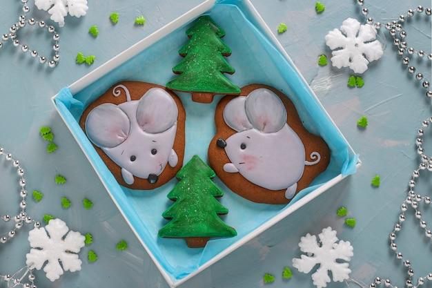 Piernikowe myszy i choinki na jasnoniebieskim stole, prezenty świąteczne lub noel wakacje, orientacja pozioma, widok z góry
