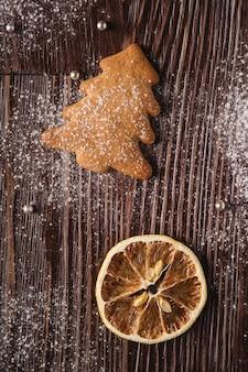 Piernikowi ciastka w bożenarodzeniowej jedlinie, sproszkowany cukier na drewnianym stole, cytrus susząca cytryna, odgórny widok