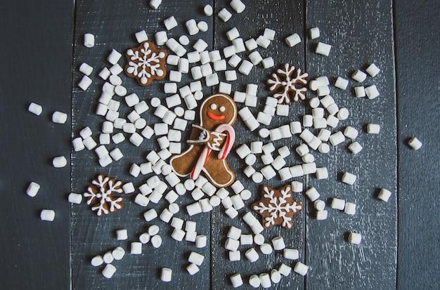 Piernikowi mężczyzna kłaść na popielatym drewnianym tle z cukierek trzciny płatkami śniegu i marshmallows.