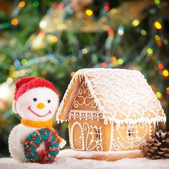 Piernikowy domek na śniegu i piękny ręcznie robiony bałwan