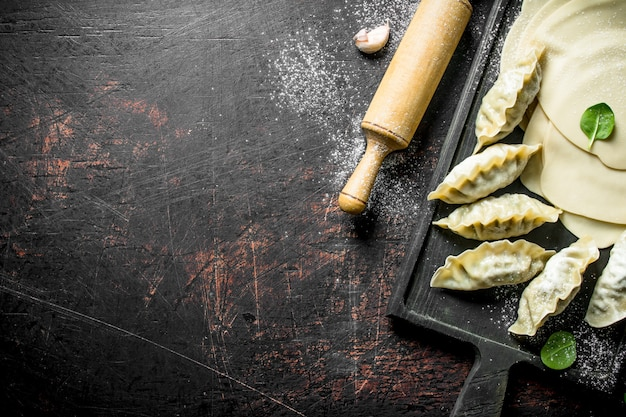 Pieróg gedza na surowo. ciasto do przygotowania pierogów gedza na ciemnym drewnianym stole
