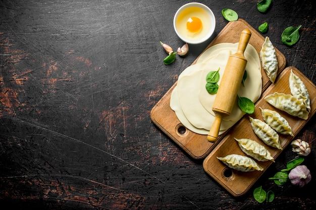 Pieróg gedza na surowo. domowa gedza z mięsem na ciemnym rustykalnym stole