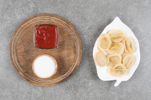 Pierogi faszerowane mięsem na białym talerzu z sosami