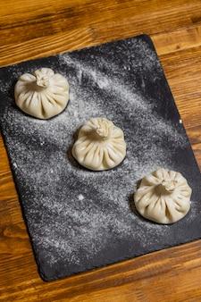 Pierogi gruzińskie chinkali z mięsem na desce z mąki czarne tło proces...