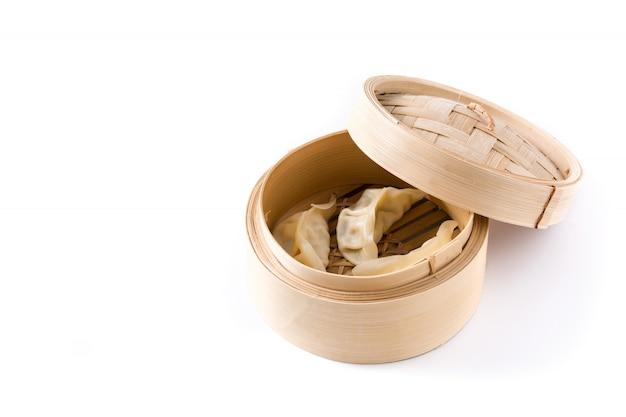 Pierogi lub gyoza podawane w tradycyjnym parowcu na białym tle