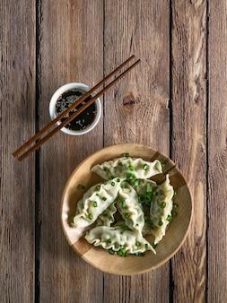 Pierogi mięsne z sosem sojowym na drewnianym talerzu w rustykalnym stole.