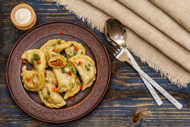 Pierogi nadziewane duszoną kapustą i kwaśną śmietaną. tradycyjne danie ukraińskie varenyky