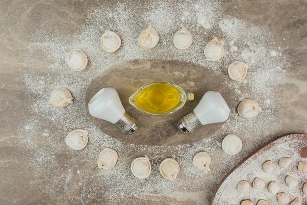 Pierogi surowe z oliwą, solą i pieprzem.