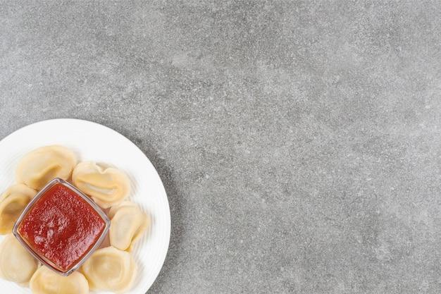 Pierogi z mięsem i keczupem na białym talerzu