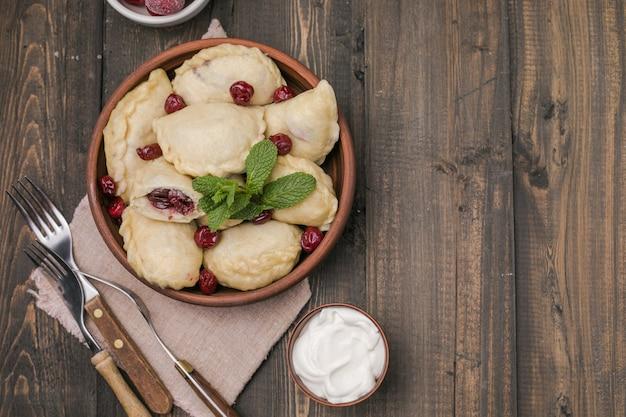 Pierogi z wiśniami. pierogi vareniki. tradycyjne ukraińskie jedzenie. gotowane i podawane z kwaśną śmietaną i jagodami