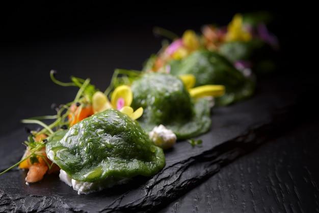 Pierogi ze szpinakiem zielone na ciemnym drewnianym stole, widok z góry. z warzywami i serem.