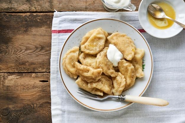 Pierogi ziemniaczane z masłem i kwaśną śmietaną na talerzu