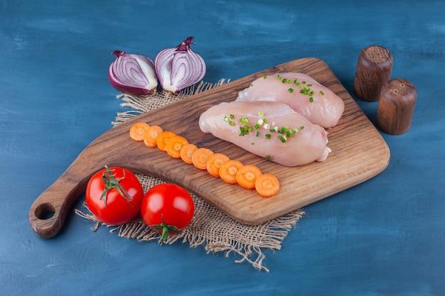Pierś kurczaka pokrojona marchewka na desce do krojenia obok pokrojonej cebuli, na niebieskim stole.