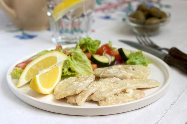 Pierś kurczaka ze śmietaną mleka i cytryny, podawana z sałatką ze świeżych warzyw.