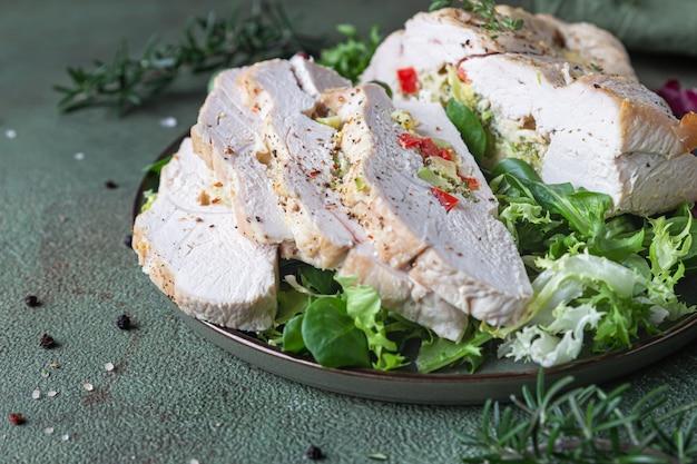 Pierś z indyka faszerowana warzywami i serem z zieloną sałatą i ziołami.