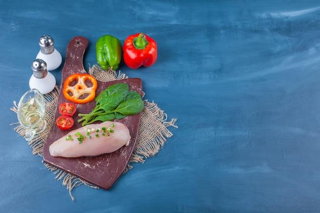 Pierś z kurczaka i warzywa na desce do krojenia, a nie na jutowej serwetce, na niebieskim stole.