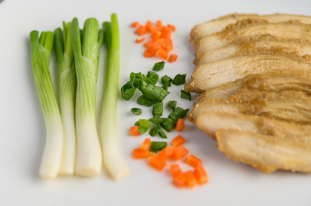 Pierś z kurczaka na parze na białym talerzu z wiosenną cebulą i posiekaną marchewką